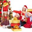 Family with children open gift box near Christmas tree. — Stock Photo #14621125