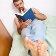 Man reading a book on the bed — Stock Photo #3286537