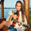 Young woman playing guitar in summerhouse on sunset — Stock Photo #4388627