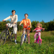 Parents with the daughter on bicycles in park a sunny day. — Stock Photo #7431672