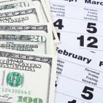 Banknotes of dollars on calendar sheets closeup — Stock Photo #22311249