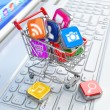 Store of laptop software. Apps icons in shopping cart. — Stock Photo #51017989