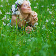 Young woman blowing a dandelion on fields — Stock Photo #10574006