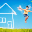 Cute girl is jumping on green meadow with abstract house on — Stock Photo #8848285