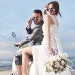 Just married couple on the beach ride white scooter — Stock Photo #5844762