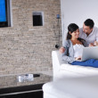 Joyful couple relax and work on laptop computer at modern home — Stock Photo #7590160