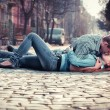 Couple of teenagers lying in street together — Stock Photo #13277239
