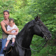 Mother, son and black horse — Stock Photo #1856484