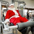 Father Christmas doing exercises in gym — Stock Photo #31882985
