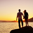 Couple watching the sun by the sea — Stock Photo #12160302
