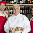 Portrait of a happy chef holding pizza with wait staff — Stock Photo #21879187