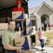 Family and worker unloading delivery van — Stock Photo #33800445