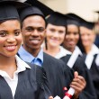 Multicultural university graduates standing in a row — Stock Photo #42486051