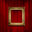 Empty golden painting frame on red curtain wall — Stock Photo #9480700