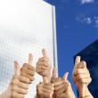 S hand with thumbs up in front of modern building — Stock Photo #7950761