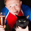 Portrait of young man holding a glass of beer and a big black cat and both looking at camera while watching tv translation of their favorite football team — Stock Photo #9249705