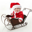 Smiling santa baby sitting in a sleigh — Stock Photo #4521163