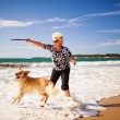 Woman playing on the beach with golden retriever — Stock Photo #13736849