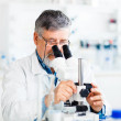 Senior male researcher carrying out scientific research in a lab — Stock Photo #10957241