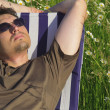 Man in meadow relaxing in deck chair — Stock Photo #4818729