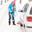 Woman snow standing with car tire chains — Stock Photo #13814380