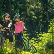 Mountain bikers resting in forest — Stock Photo #28065441