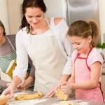 Three generation of women baking dough kitchen — Stock Photo #9548013