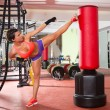Crossfit woman kick boxing with red punching bag — Stock Photo #25466033