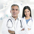 Expertise gray hair doctor beautiful nurse hospital — Stock Photo #5309284