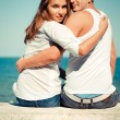 Happy young couple sitting by blue sea over blue sky background — Stock Photo #17600039