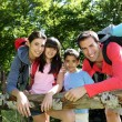 Family on a hiking day resting along fence — Stock Photo #13937022
