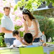 Mother serving lunch to kids in home garden — Stock Photo #13937413