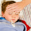 Sick child boy being checked for fever and illness while resting in bed — Stock Photo #10504515