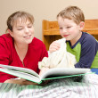 Mother reads bedtime story to young boy in his room at night — Stock Photo #9677436