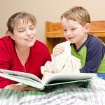 matka czyta bajkę na dobranoc młody chłopiec w jego pokoju w nocy — Zdjęcie stockowe #9677436