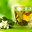 Cup of green tea with jasmine flowers on wooden table on green background — Stock Photo #11920410