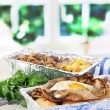Food in boxes of foil on napkin on wooden board on window background — Stock Photo #29533571