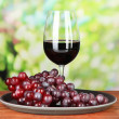Ripe grapes and glass of wine, on bright background — Stock Photo #31731263