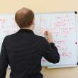Man writing math formulas on a white-board — Stock Photo #8116062