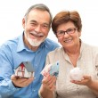 Senior couple holding a house model and piggy bank — Stock Photo #39862799