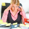Tired business woman sitting at workplace overwhelmed with sticky reminder — Stock Photo #8634112