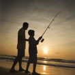 Man and young boy fishing in surf Man and young boy fishing in surf Man and young boy fishing in surf — Stock Photo #9498360