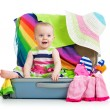 Baby girl sitting in suitcase with things for vacation travel — Stock Photo #25596909