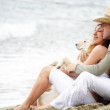 Young couple with a dog sitting on the beach — Stock Photo #8980033
