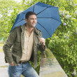 Man in park with blue umbrella — Stock Photo #11385304