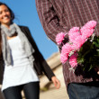 Boy surprising girlfriend with flowers — Stock Photo #9725399