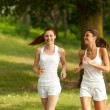 Two young woman running in a park — Stock Photo #9765401