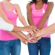 Women wearing breast cancer ribbons putting hands together — Stock Photo #28047125