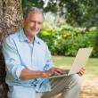Smiling old man with a laptop — Stock Photo #29446281