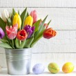 Spring easter tulips in bucket on white vintage planks — Stock Photo #21999073